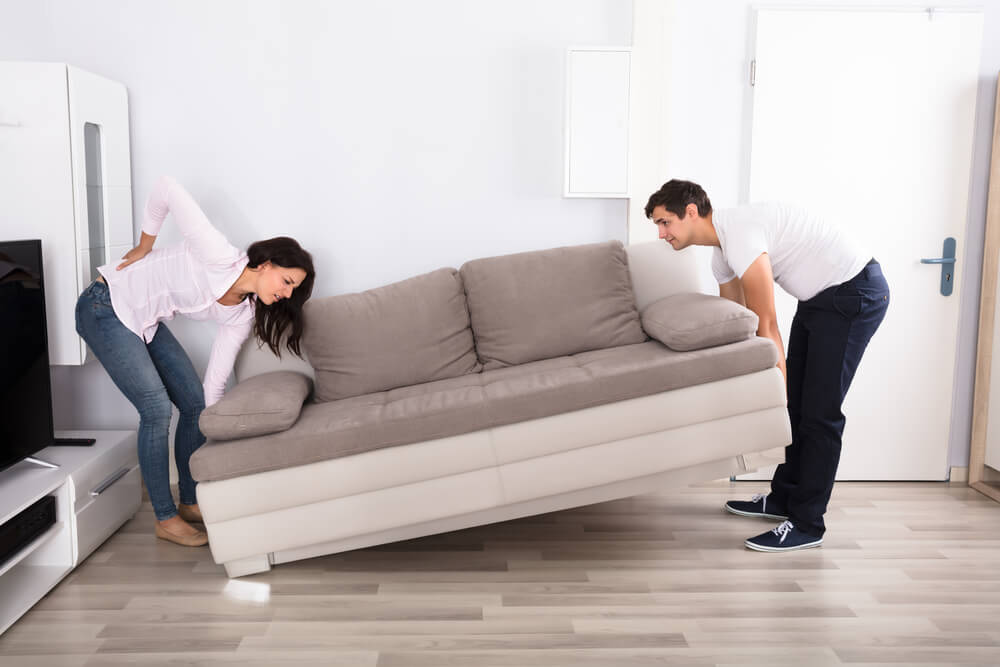 a couple is moving a sofa