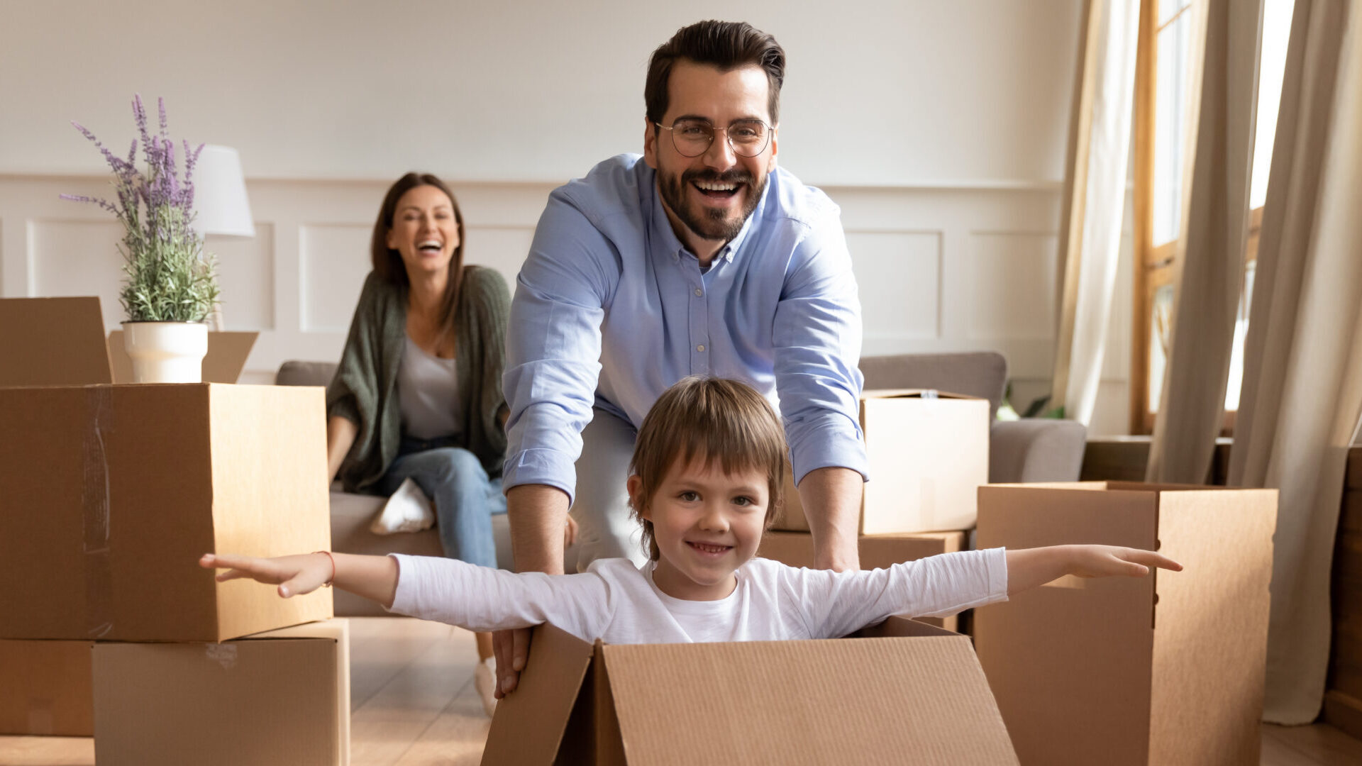 child in box being pushed by dad