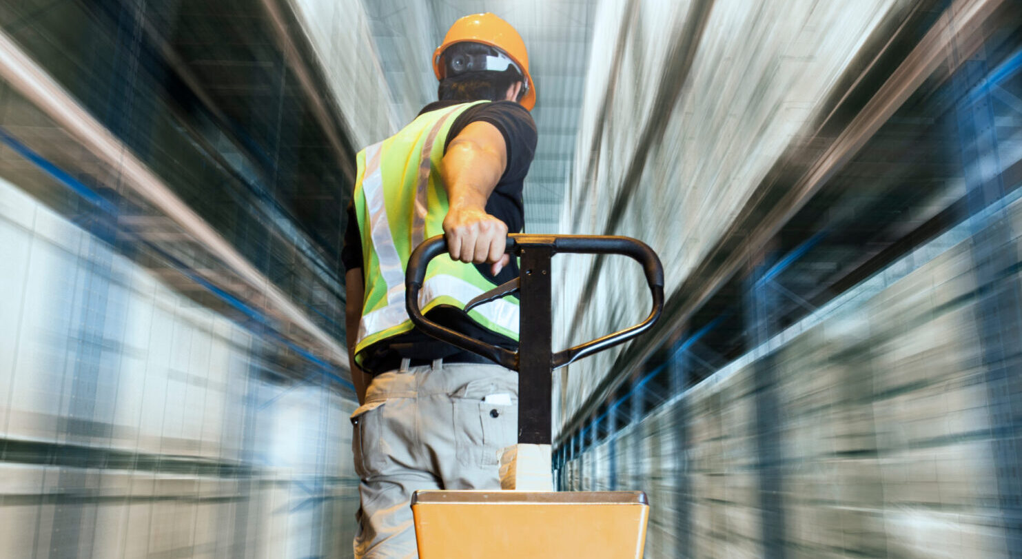 man in warehouse pulling boxes